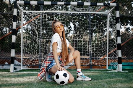 Funky young blonde teenage hipster girl posing with serious face with soccer ball in front of goal post at the stadium. Freedom concept.