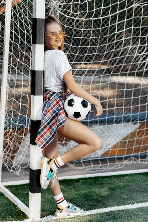 Charming young blonde hipster girl posing with soccer ball in front of goal post at the stadium. Freedom concept. Zdjęcie Seryjne