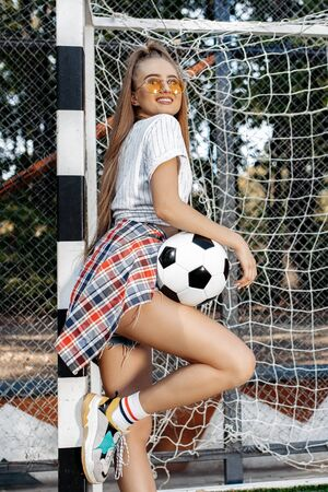 Happy young blonde hipster girl posing with soccer ball in front of goal post at the stadium. Freedom concept.