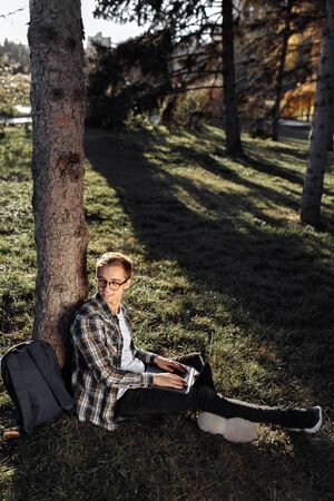 Young male student in casual outfit using notebook or laptop while sitting on the grass at the park. Foto de archivo - 134557950