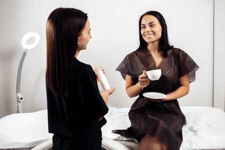 Coffee brake. Cosmetologist and patient have a discusion in cosmetology center. Stock Photo