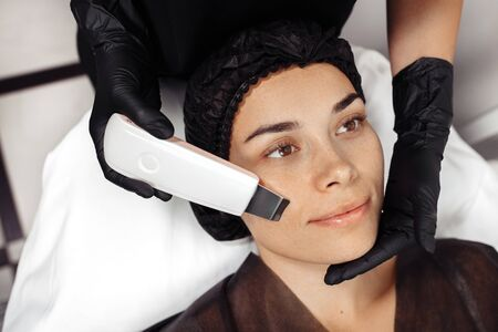 Cosmetologist make face while procedure ultrasound cavitation or facial peeling in cosmetology cabinet.