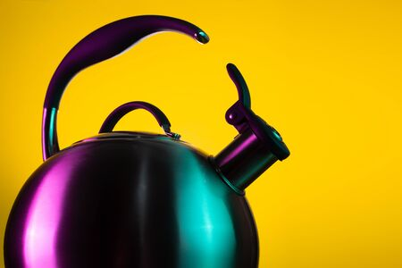 Close-up photo of stainless steel kettle in neon light over yellow background.