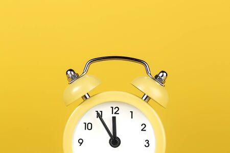 Yellow round alarm clock on the yellow background.