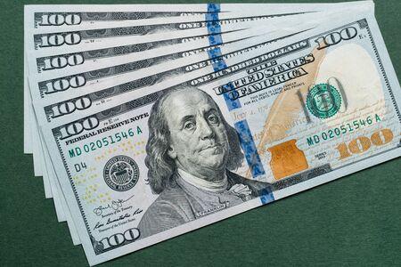 Pila di banconote da cento dollari americani su sfondo verde.