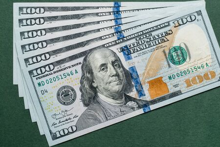 Stack of one hundred american dollars bills over green background.