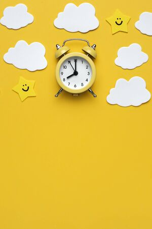 Yellow round alarm clock, moon, stars and white clouds on the yellow background.