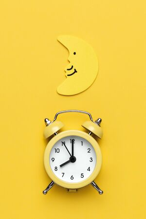 Yellow round alarm clock and moon on the yellow background. Banco de Imagens