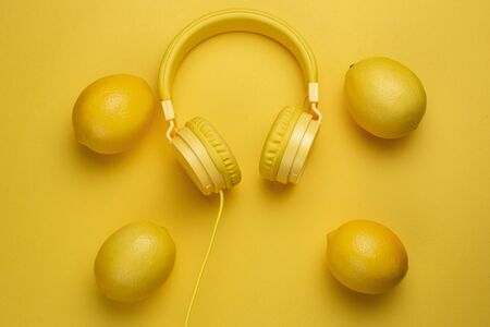 Yellow headphones decored with lemons on yellow background. Music concept.