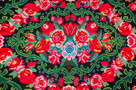 Colorful traditional vintage handmade folk carpet with floral shapes and motifs of Moldovian or Romanian traditions.