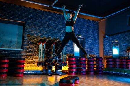 Shot of fit young woman using step platform at gym. Aerobic and fitness exercises. Stock Photo