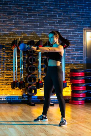 Sporty young woman workout in the gym with kettlebell. Imagens
