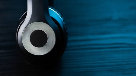 Black headphone on dark wooden background. Stylish wireless headset in neon light.