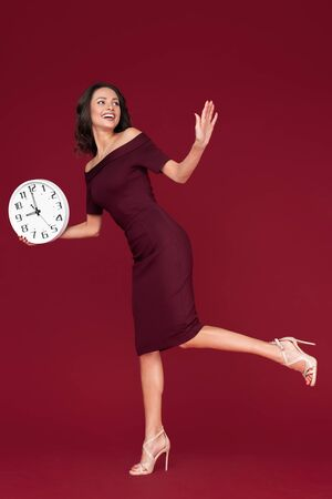 Full lengh photo of happy young modern business woman in maroon dress holding a clock over red background.