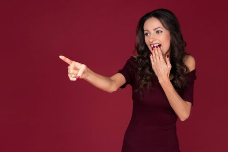 Shocked elegant young woman in maroon dress point fingers away over red background.