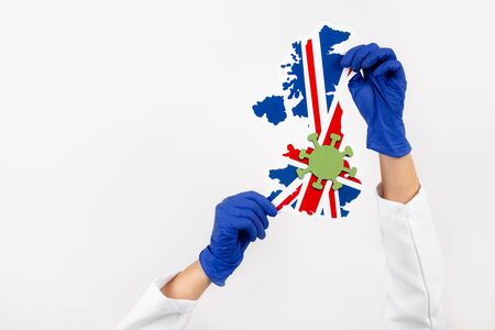 Doctor or nurse holding UK map and flag. Coronavirus outbreak and pandemic concept. 2019-nCoV.