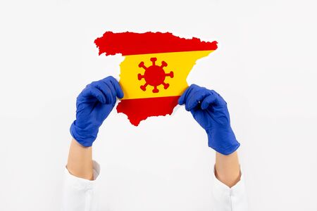 Doctor or nurse holding Spain map and flag. Coronavirus outbreak and pandemic concept. 2019-nCoV.
