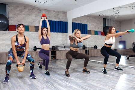 Group of four young sporty girls workout with kettlebells in fitness class. Standard-Bild