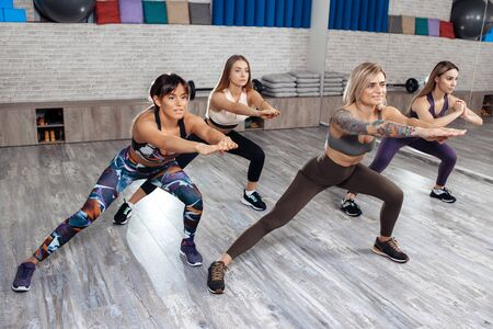 Group of four young sporty girls doing weight loss workout in fitness class. Sport, fitness and lifestyle concept.