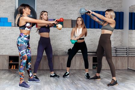 Group of four young powerful girls workout with kettlebells in fitness class. Functional resistance training. Stok Fotoğraf