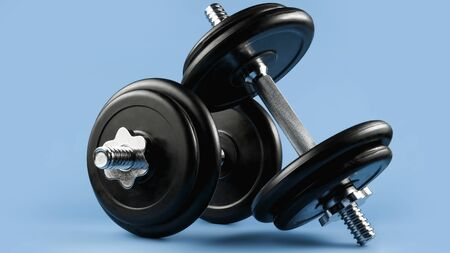 Professional dumbbell and weight plates over blue background. Gym equipment. Fitness concept.