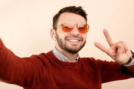 Happy bearded young man in casual outfit wearing yellow sunglasses showing peace gesture over beige background.