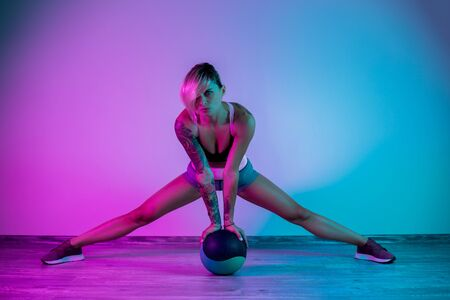 Fit young blonde woman exercise with medicine ball in gym in neon lights. Foto de archivo