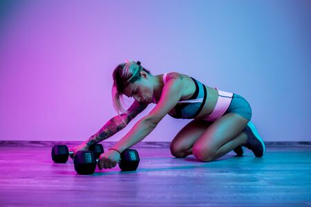 Athletic young blonde woman rest after heavy dumbbell exercise in the gym in neon lights.