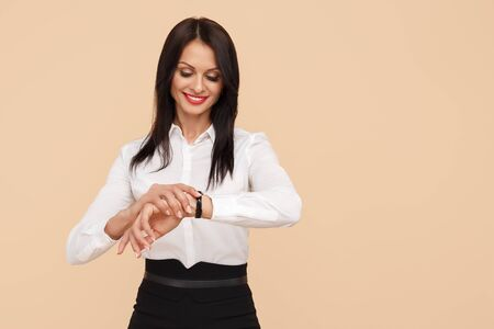 Photo of pretty young modern business woman look at watch over beige background.