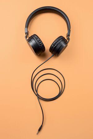 Photo of stylish modern black headphones over beige background Archivio Fotografico
