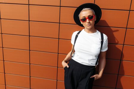 Serious hipster young woman wearing red sunglasses and black hat stay near wall of modern building.