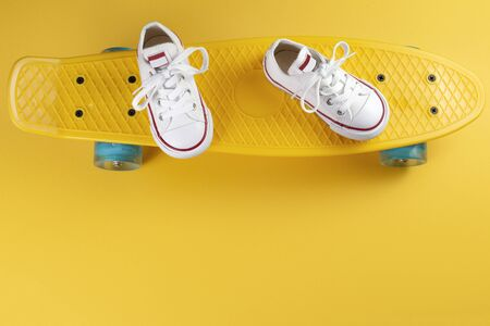 Photo of white sneakers on the skateboard or penny board over yellow background 版權商用圖片