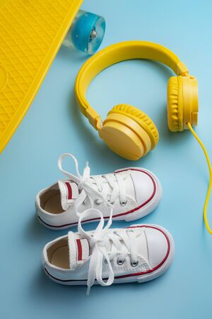 Yellow headphones, white sneakers and traditional style soccer ball over blue background