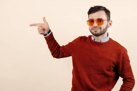Cheerful bearded man in casual outfit wearing sunglasses pointing finger away on beige background. Stock fotó