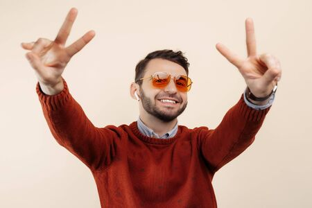 Gleeful bearded man in casual outfit wearing sunglasses showing peace gesture on beige background.