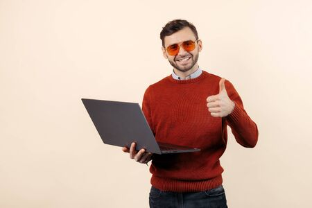 Handsome bearded young man in casual outfit with notebook or computer show thumbs up over beige background. Stock fotó