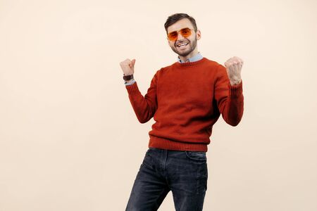 Delighted bearded man in casual outfit wearing sunglasses celebrating over beige background. Success and winner.