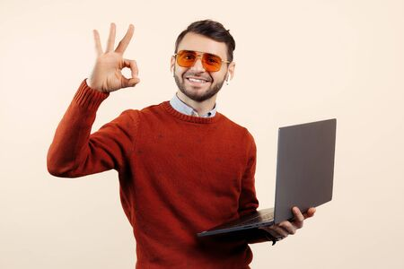 Smile bearded young man in casual outfit with notebook or computer show ok gesture over beige background.