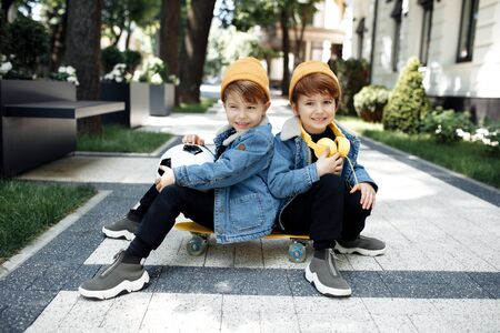 Two gleeful twin boys sitting on the skateboard or pennyboard looking each over up in the street. 스톡 콘텐츠