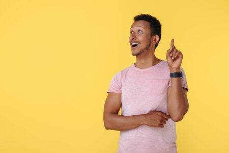 Attractive african american young man pointing finger up over yellow background. Idea concept. Looking away.