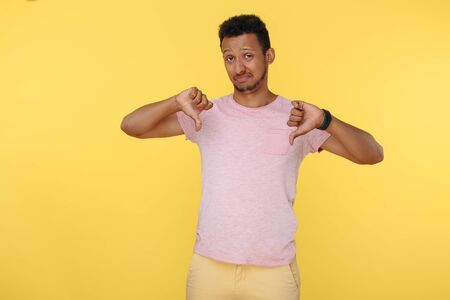 Unhappy african american young man show thumbs down over yellow background.