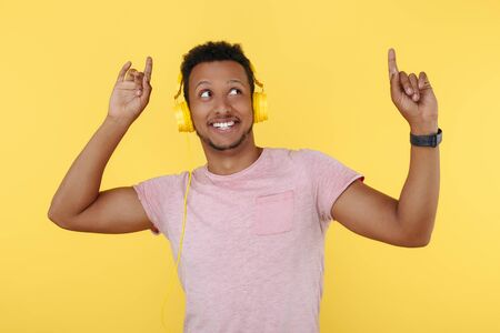 Positive african american young man listening music in headphones and dancing over yellow background.