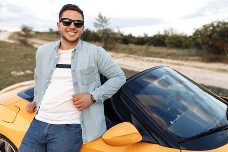 Cheerful smiling young man staying beside yellow convertible car. Freedom, travel and careless concept. Foto de archivo