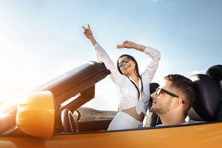 Cheerful young couple going on a long drive in a convertible car on the sunset. Freedom, travel and love concept.