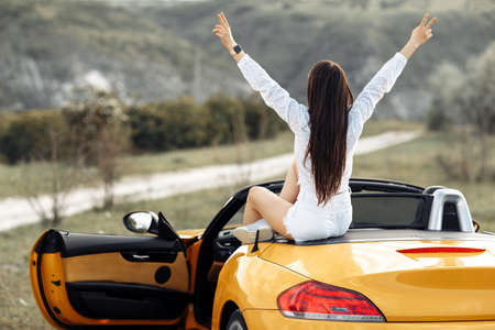Cheerful young woman sitting in yellow convertible car showing peace gesture. Adventures and travel concept.