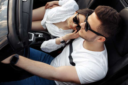 Relaxed young couple going on a long drive in a convertible car on the sunset. Freedom, travel and love concept.