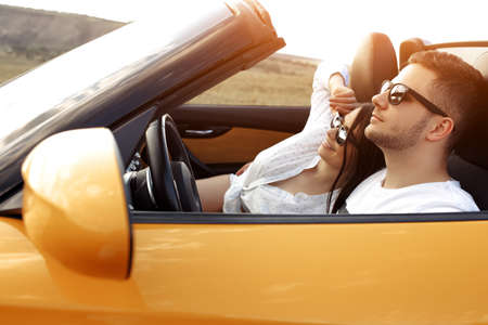 Modern young couple going on a long drive in a convertible car on the sunset. Freedom, travel and love concept.