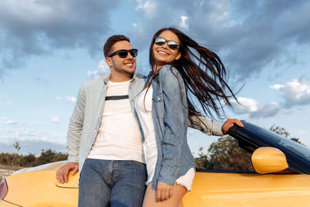 Gleeful young couple staying beside a yellow convertible car. Freedom, travel and love concept.