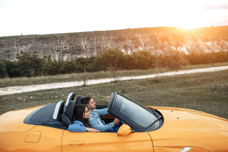 Cheerful young couple going on a long drive in a convertible car. Freedom, travel and love concept.