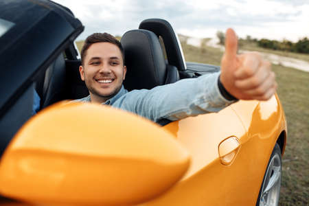 Poisitive smiling young man sitting in yellow convertible car showing thumb up. Freedom, travel and careless concept. Foto de archivo